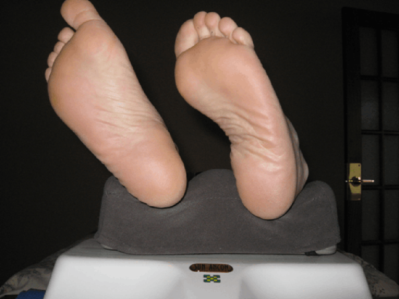 Feet on the Oxygen Massage Exerciser device